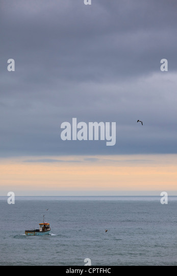 Lone fishing boat heading out to sea at Beer, Devon, UK - Stock Image