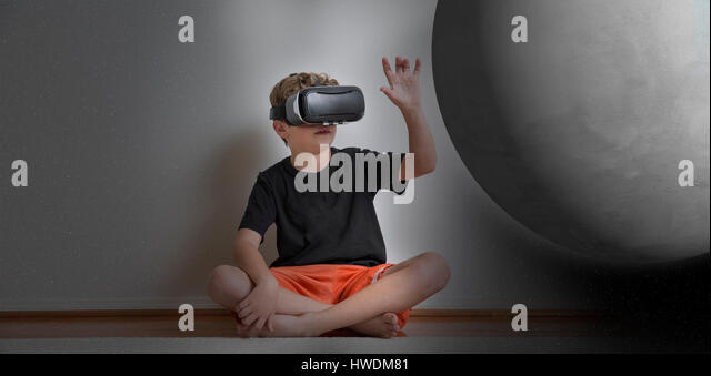 Young boy sitting cross legged, wearing virtual reality headset, reaching out to touch planet, digital composite - Stock-Bilder