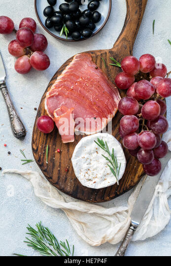 Appetizer plate with meat, grapes, cheese and olives. Antipasti or tapas concept. Top view - Stock Image
