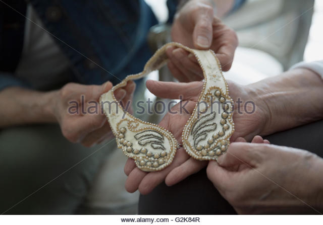 Close up senior women holding delicate pearl collar - Stock Image
