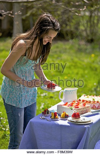 A young woman by a cake buffet outdoors - Stock Image