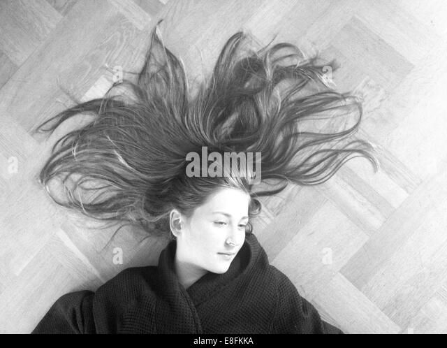 Stockholm, Sweden Girl Laying On Wooden Floor With Her Hair Out - Stock Image