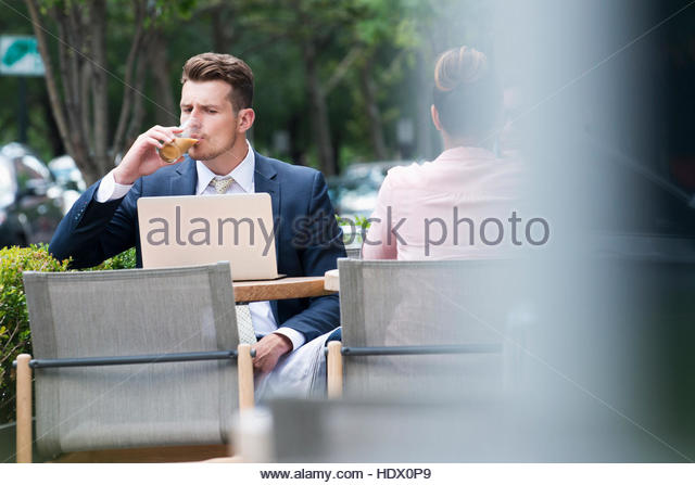 Businessman drinking and reading laptop at cafe outdoors - Stock Image