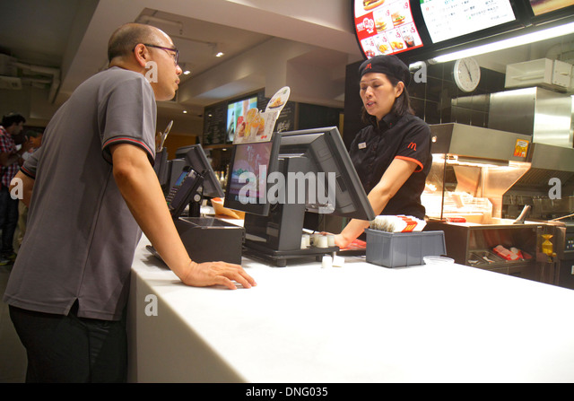 Hong Kong China Island Sheung Wan Des Voeux Road Central McDonald's restaurant fast food counter customer employee - Stock Image