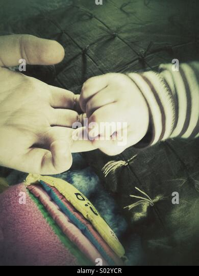 Childhood, baby's hand holding on to teenager's hand, retro filter - Stock Image