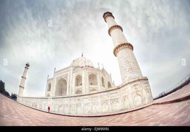 Woman in red walking near Taj Mahal at dramatic sky in Agra, Uttar Pradesh, India - Stock Image
