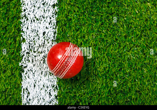 Photo of a cricket ball on a grass next to the white line, shot from above. - Stock Image