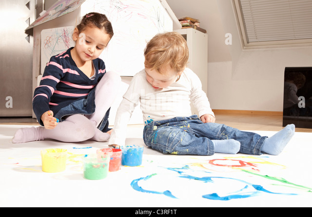 Girl and boy playing with finger paint - Stock Image