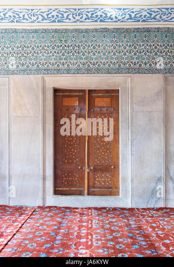 Wooden aged engraved door, marble wall and ceramic tiles with floral blue decorative patterns, Sultan Ahmet Mosque - Stock Image