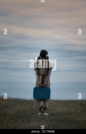 a girl in a vintage dress with suitcase - Stock-Bilder