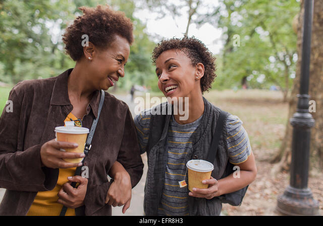 Two mature female friends drinking takeaway coffee whilst strolling  in park - Stock-Bilder