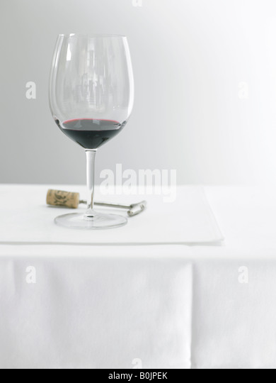 red wine glass on table with corkscrew - Stock Image