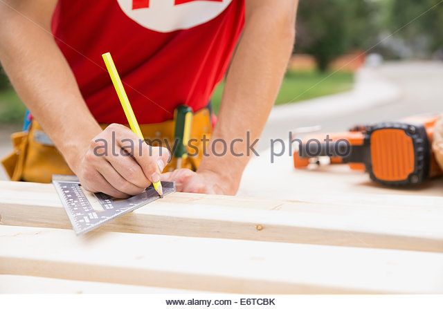 Volunteer marking wood with pencil - Stock Image