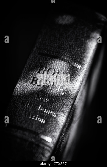 Holy Bible against a dark background. Monochrome - Stock Image