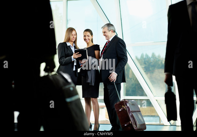 Three business people meeting in the airport - Stock Image