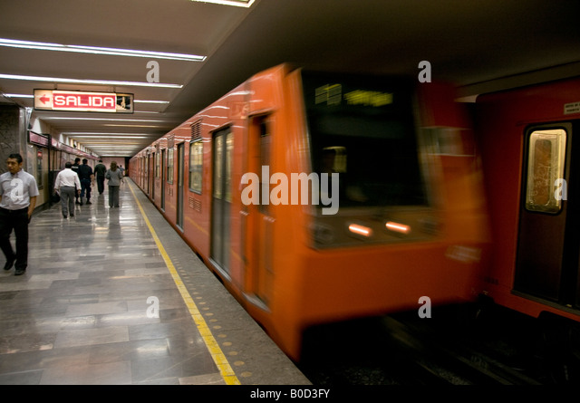 Speeding orange-coloured underground metro train in Mexico City. Showing passengers on the platform and the SALIDA - Stock Image