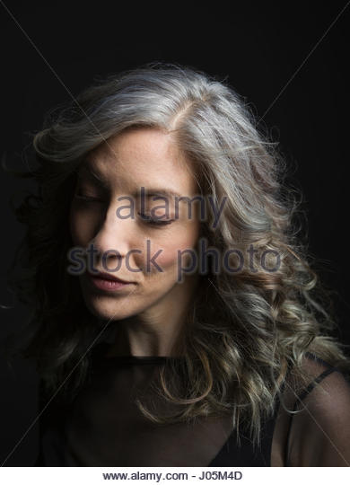 Serious, pensive woman with gray hair looking down against black background - Stock Image