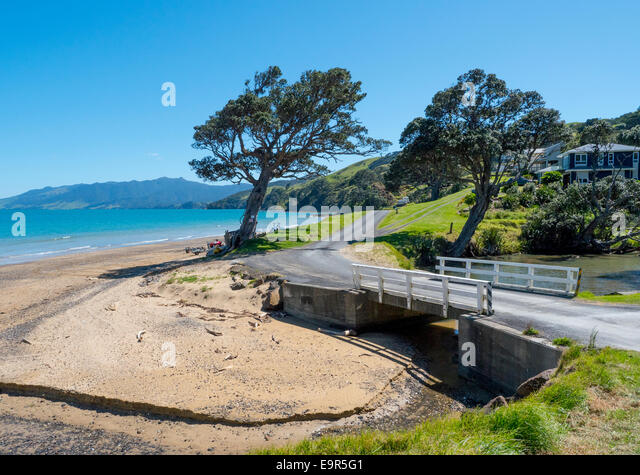 Gravel road and bridge, Waitete Bay, Colville Road, Coromandel, New Zealand - Stock Image