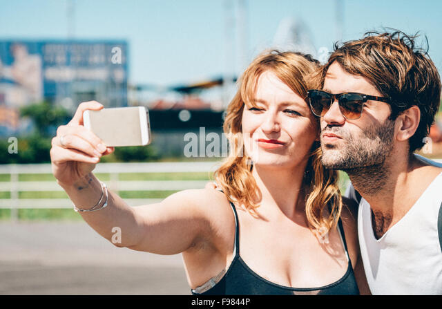 Happy Friends Clicking Selfie On Smart Phone While Standing Outdoors - Stock Image