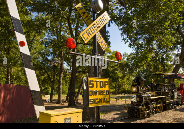 San Antonio Zoo miniature train Brackenridge Park railroad crossing with working stop gates Texas TX - Stock Image