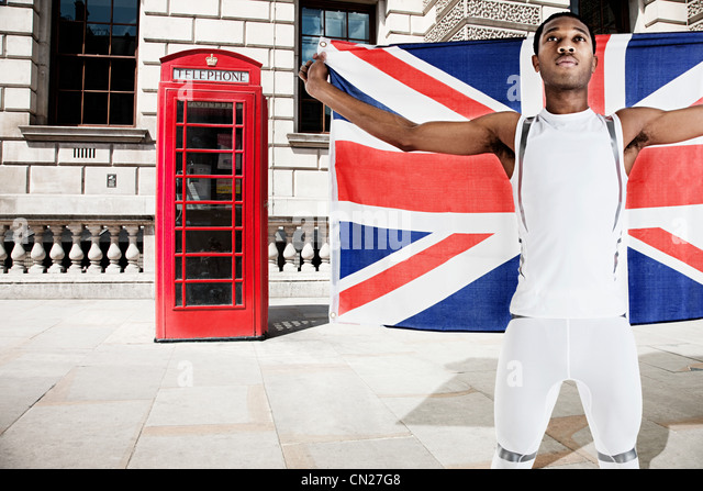 Olympic competitor with Union Jack and red telephone box in background - Stock Image