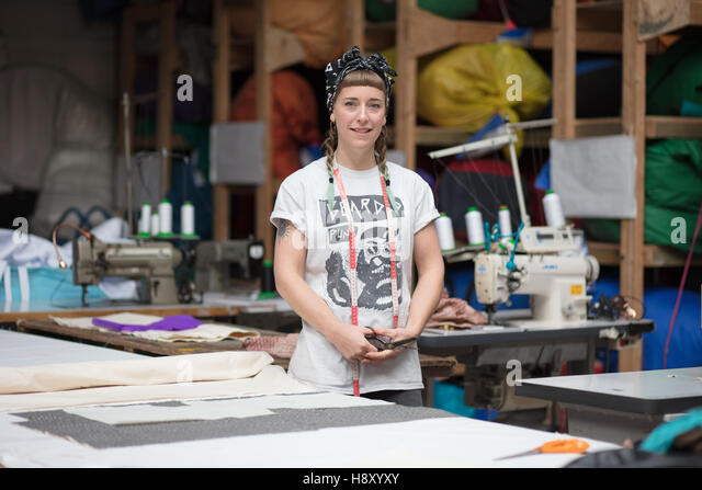 Portrait of a young tattooed seamstress in a factory environment - Stock Image