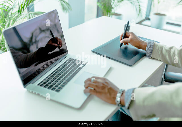 Graphics designer using digitizer with its reflection showing on the notebook screen - Stock Image
