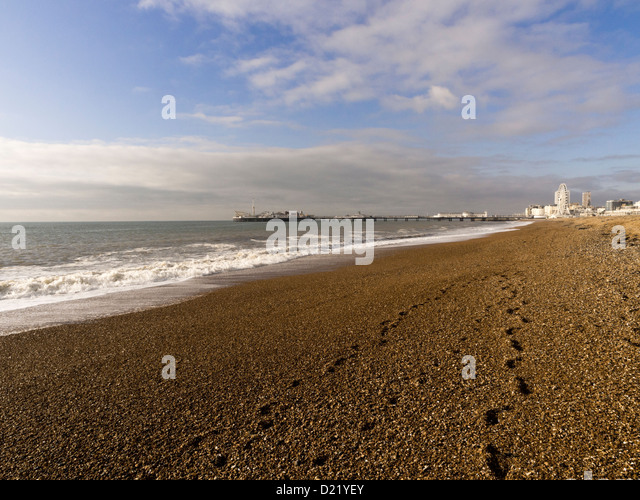 Footsteps in the shingle on Brighton beach towards Brighton Pier, East Sussex, UK - Stock Image