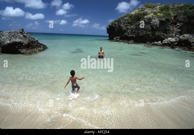 West Indies St. Kitts Southeast Peninsula Friar's Bay cove boy father swimming - Stock Image