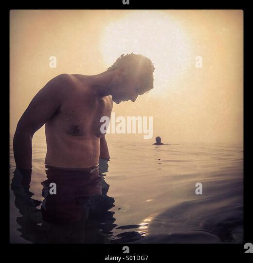 A man looks at the sallow sea waters while having an early morning swim - Stock Image