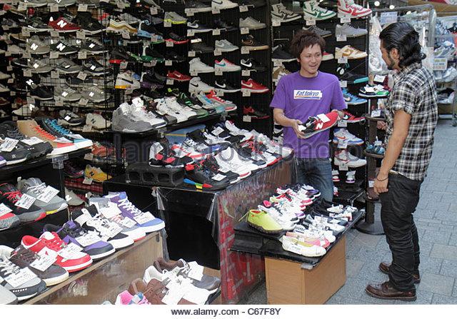 Tokyo Japan Ueno Chuo Dori kanji hiragana katakana Japanese English characters symbols athletic shoe store shopping - Stock Image