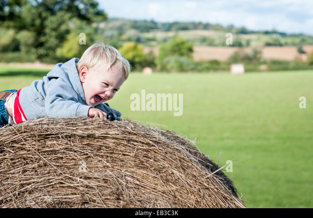 Boy crawling on hay bale laughing - Stock Image