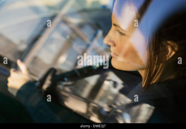 View of businesswoman driving car through window - Stock Image