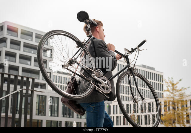 Young businessman carrying bicycle, Munich, Bavaria, Germany - Stock-Bilder