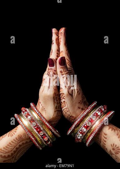 Woman hands with henna in Namaste mudra on black background - Stock-Bilder