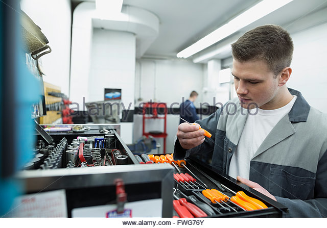 Mechanic selecting tool from toolbox auto repair shop - Stock Image