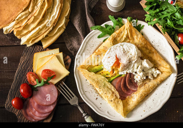 Crepe galette with meat, avocado, soft white cheese and poached egg on white plate - Stock Image