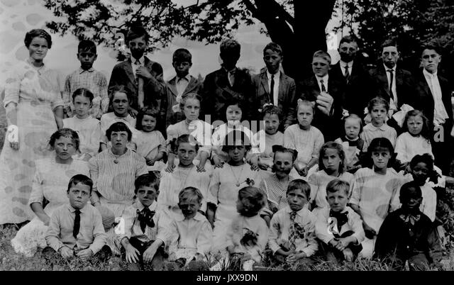 Landscape shot of schoolchildren, all seated in grass under a tree, one row standing, all boys and girls wearing - Stock Image