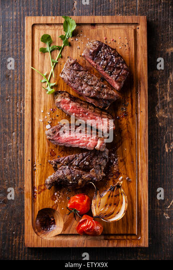Sliced medium rare grilled Beef steak Ribeye with grilled onions and cherry tomatoes on cutting board on wooden - Stock Image