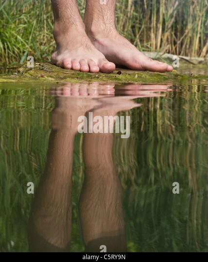 Austria, Vienna, Reflection of man's feet on lakeshore, close up - Stock Image