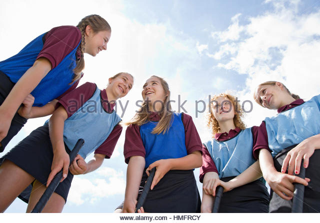 Smiling middle schoolgirls playing field hockey talking in physical education class - Stock-Bilder
