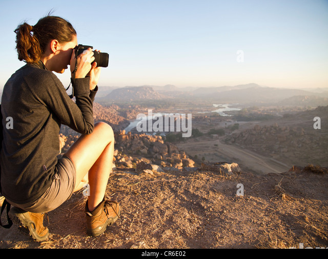 India, Karnataka, Young female tourist photographing on top of hill in Hampi - Stock Image
