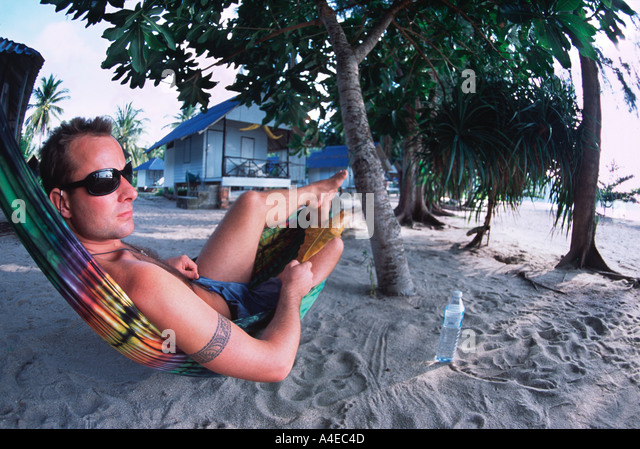 Young Man with tattoo in Hammock on beach Thailand - Stock Image