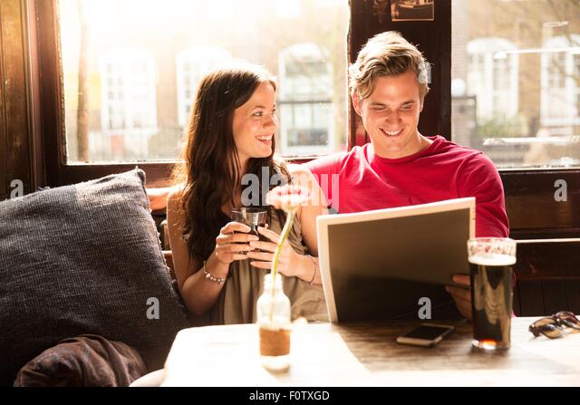 Couple enjoying drinks looking at newspaper together - Stock Image