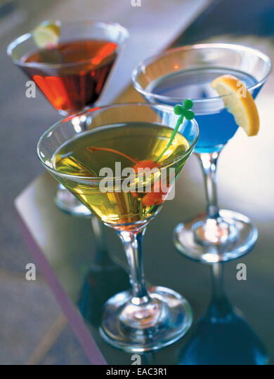 3 colorful martinis on bar counter - Stock Image