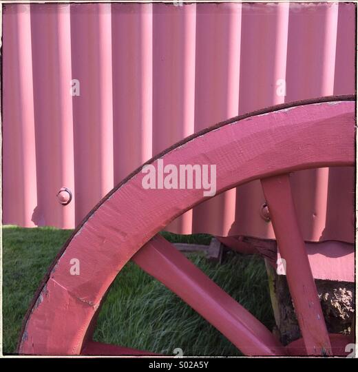 Part of  a cart wheel and siding painted in bright pink - Stock Image