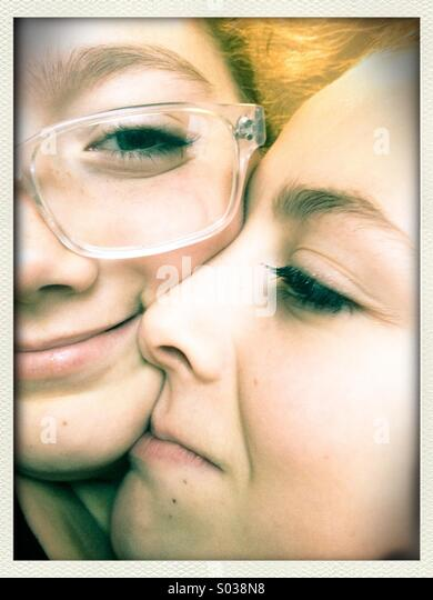 Faces of two young sisters smiling and embracing - Stock Image