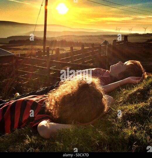 Children relaxing in the evening sun - Stock Image