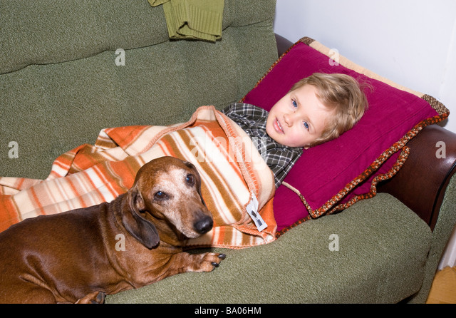 3 year old boy feeling not well resting with a dog on sofa Poland - Stock Image