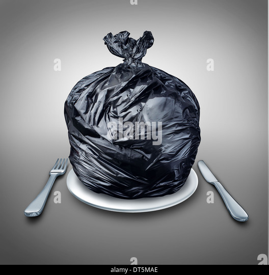 Food garbage and poor nutrition concept as a table setting with a black plastic garbage bag on a dinner plate with - Stock Image
